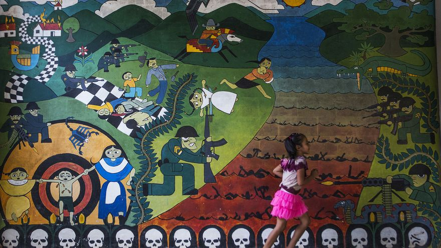 Una niña camina junto a uno de los murales que recuerdan el conflicto armado interno de El Salvador en Carasque (Foto: Oliver de Ros)